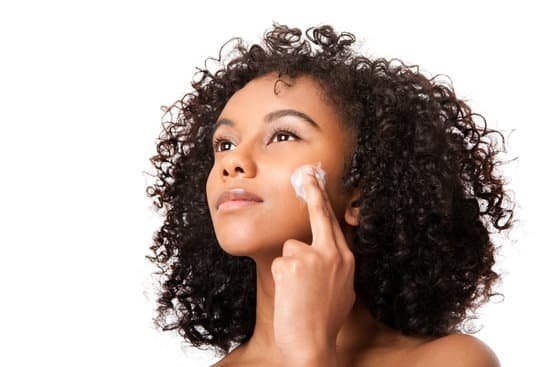 beautiful young african woman applying sunblock lotion to face